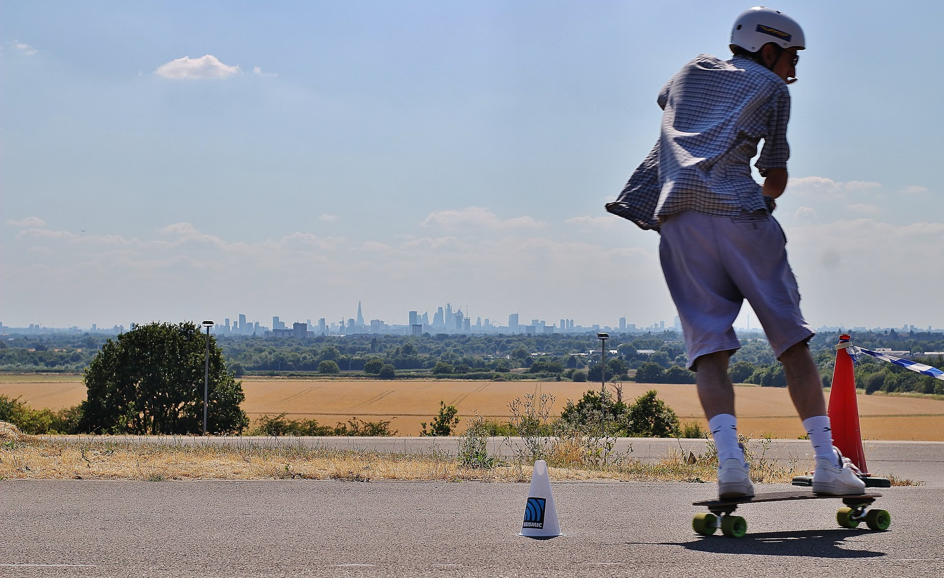 Chris Charalambous passes in front of the London skyline in the distance.